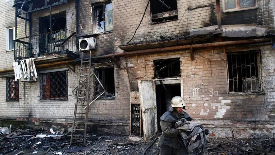 A firefighter carries an additional water hose at damaged apartment building after shelling in the town of Donetsk, eastern Ukraine, Wednesday, Sept. 17, 2014. Ukraine moved to resolve months of crisis Tuesday by strengthening ties to Europe and loosening some controls over the country's rebellious eastern regions where it has been fighting Russian-backed separatists. (AP Photo/Darko Vojinovic)