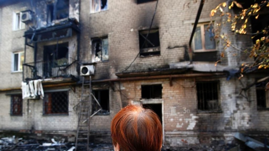 A woman cries in front of her damaged apartment building after shelling in the town of Donetsk, eastern Ukraine, Wednesday, Sept. 17, 2014. Ukraine moved to resolve months of crisis Tuesday by strengthening ties to Europe and loosening some controls over the country's rebellious eastern regions where it has been fighting Russian-backed separatists. (AP Photo/Darko Vojinovic)