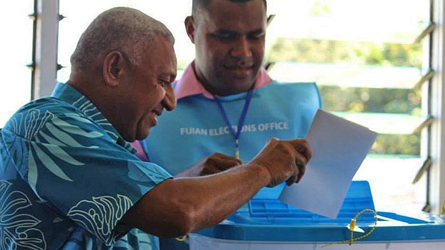 Fiji's military ruler Voreqe Bainimarama, left, casts his vote in a national election in Suva, Fiji, Wednesday, Sept. 17, 2014. Thousands of Fijians got their first chance to vote in eight years in an election that promises to finally restore democracy to the South Pacific nation of 900,000. (AP Photo/Pita Ligaiula)