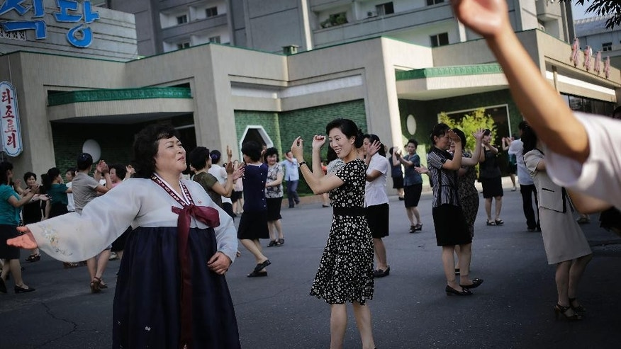 FILE - In this July, 27, 2013 file photo, North Koreans dance in celebration of the 61st anniversary of the armistice that ended the Korean War,  in downtown Pyongyang. Time and again, Americans over the years have slipped into poor, deeply suspicious, fervently anti-American North Korea, crossing a border that tens of thousands of desperate North Koreans have crossed in the opposite direction, at great risk. Whatever their reasons, Americans detained in North Korea, including the three currently there, are major complications for Washington, which must decide between letting a U.S. citizen languish and providing Pyongyang with a huge propaganda victory by sending a senior U.S. envoy to negotiate a release.  (AP Photo/Wong Maye-E, File)