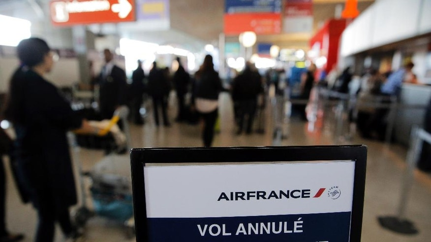 "A traveller walks past a board reading ""canceled flight"", at Paris Charles de Gaulle airport, in Roissy, near Paris, Wednesday, Sept. 17, 2014. Air France canceled at least half its flights around the world on Monday as pilots began a weeklong strike, highlighting the trouble Europe's flagship airlines face in keeping up with low-cost competitors. (AP Photo/Christophe Ena)"