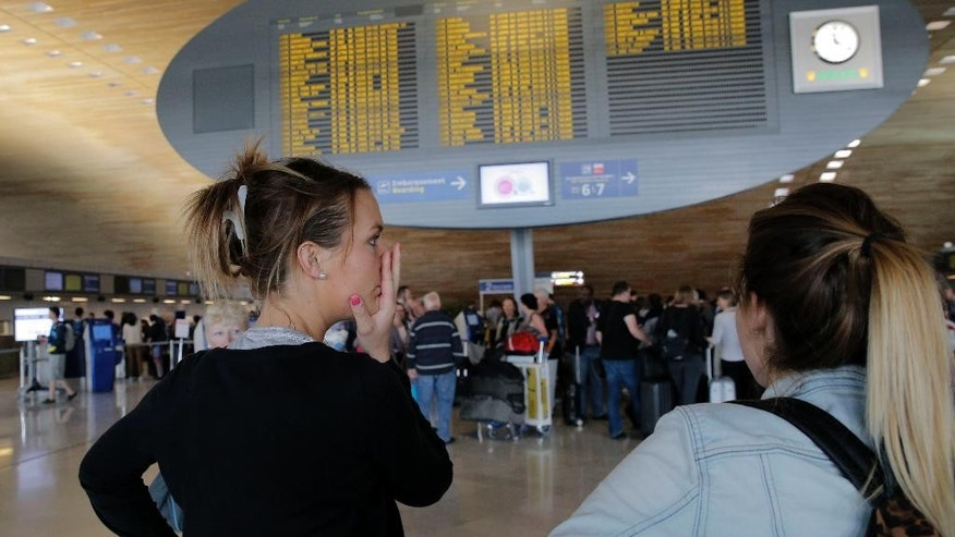 Margaux Hengel, right, and Stephanie Leon of France react after their flight is canceled at Paris Charles de Gaulle airport, in Roissy, near Paris, Wednesday, Sept. 17, 2014. Air France canceled at least half its flights around the world on Monday as pilots began a weeklong strike, highlighting the trouble Europe's flagship airlines face in keeping up with low-cost competitors. Both 24-year-old medical workers, already made a sacrifice before dawn on Wednesday. They hurriedly bought tickets on a 4-hour train to catch their flight to the Caribbean after their first-leg flight from Brest, in western France, to Paris was canceled. (AP Photo/Christophe Ena)