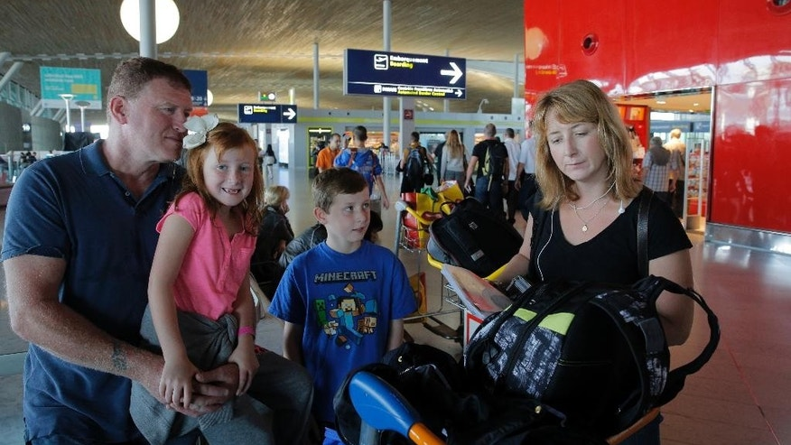 Katie Ford of the U.S.  right, checks her flight ticket as her husband Steve, left, her daughter Madie, second right, and her son Charlie look on at Paris Charles de Gaulle airport, in Roissy, near Paris, Wednesday, Sept. 17, 2014.  Air France canceled at least half its flights around the world on Monday as pilots began a weeklong strike, highlighting the trouble Europe's flagship airlines face in keeping up with low-cost competitors. For Steve Ford, who with his family had planned to take Air France to Birmingham, England for a wedding, it's understandable: Pilots have tens of thousands of lives in their hands every day. (AP Photo/Christophe Ena)