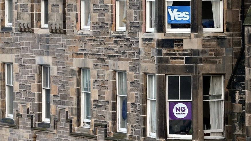 "Adjoining apartments display No and Yes signs in their windows in in Edinburgh, Scotland, Tuesday, Sept. 16, 2014. The two sides in Scotland's independence debate are scrambling to convert undecided voters, with just two days to go until a referendum on separation. Anti-independence campaigners are pushing home their message that a ""No"" vote doesn't mean the status quo. The three main British political parties are promising Scotland greater powers, including tax-raising authority, if it remains part of the United Kingdom. The Yes campaign says the promises are vague and reveal the No side's desperation, with polls suggesting the outcome will be close. Scottish Deputy First Minister Nicola Sturgeon said ""the only way to guarantee the real powers we need in Scotland is to vote Yes."" (AP Photo/Scott Heppell)"