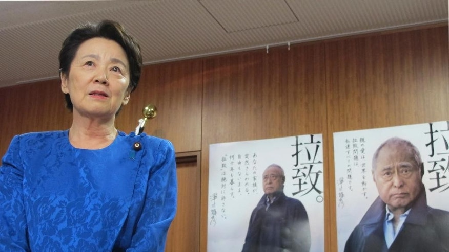 "Japanese Minister in charge of abductions Eriko Yamatani speaks during an interview with journalists at her office in Tokyo Wednesday, Sept. 17, 2014. Yamatani urged North Korea to quickly release the results of a new investigation into the fate of dozens, possibly hundreds, of Japanese believed to have been abducted by the North's agents in the 1970s and '80s. Yamatani said it is extremely regrettable that North Korea hasn't informed Japan of the timing or other details of its expected announcement. Japanese on the posters read: ""Abduction, we are sure to take them back."" (AP Photo/Mari Yamaguchi)"