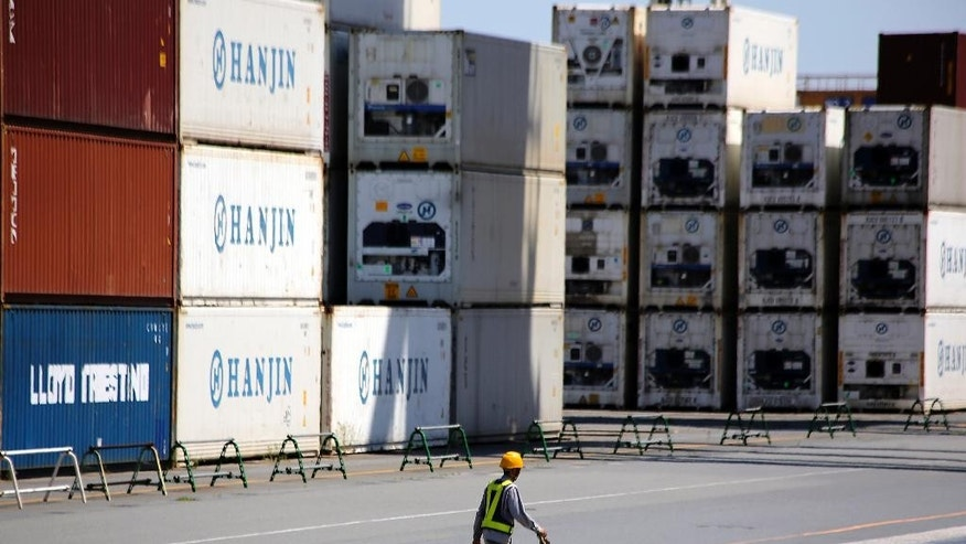 FILE - In this Aug. 20, 2014 file photo, a port worker walks past a piles of cargo at a container terminal in Tokyo. Japan has logged a 948.5 billion yen ($8.8 million) trade deficit in August, the 26th straight month of red ink, as weak demand at home hit imports while exports also fell. The Finance Ministry reported Thursday, Sept. 18, 2014 that exports fell 1.3 percent from a year earlier to 5.71 trillion yen ($53.3 billion) while imports dropped 1.5 percent to 6.65 trillion yen ($62.1 billion). (AP Photo/Eugene Hoshiko, File)