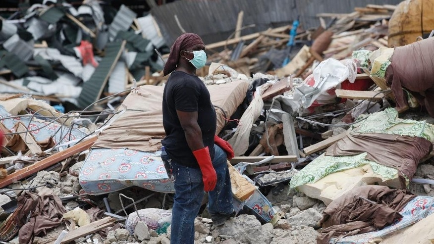 A rescue worker takes part in the search of the rubble of a collapsed building belonging to the Synagogue Church of All Nations in Lagos, Nigeria Wednesday, Sept. 17, 2014. A Nigerian televangelist whose followers across Africa and beyond believe he has powers of healing and prophesy is now beset by crisis after one of his buildings collapsed, killing at least 70 people amid allegations that church officials didn't cooperate with rescuers. The exact circumstances of the disaster as well as the death toll remained unclear on Wednesday, five days after the disaster at a multistory guesthouse and shopping area for T.B. Joshua's Synagogue, Church of All Nations, on the outskirts of Lagos, Nigeria's commercial capital. ( AP Photo/Sunday Alamba)