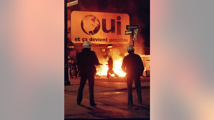 "FILE - In this Monday, Oct. 30, 1995 file photo, police watch a fire burn underneath a ""Oui"" pro-separatist sign after federalists won the Quebec independence referendum. Quebec has always been apart from the rest of Canada by keeping French as its first tongue. (AP Photo/The Canadian Press, Tom Hanson)"