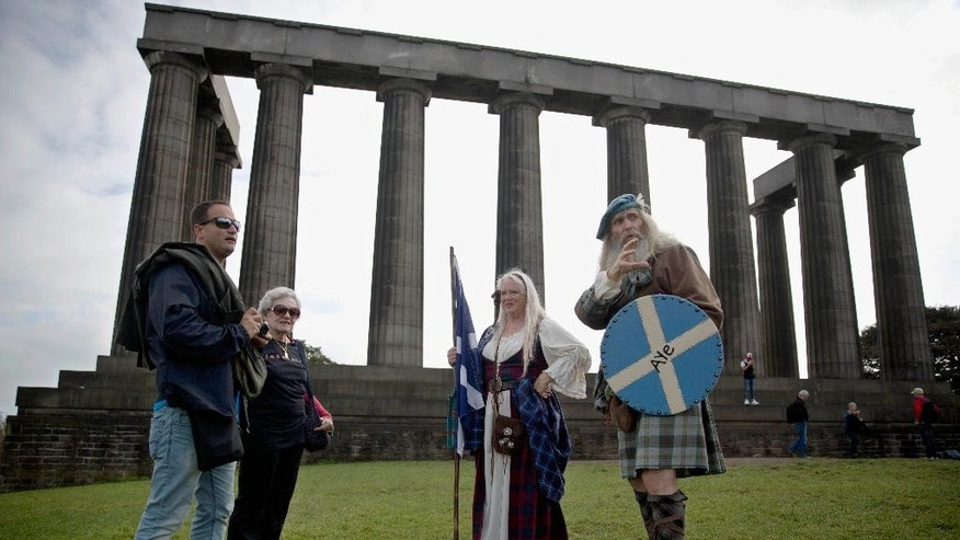 Scotland independence supporters and members of a Scottish historical re-enactment group, Ed Hastings, right, and his wife, Sandy Hastings, second right, wearing historical Scottish clothing, talk with tourists at Scotland's National Monument on Calton Hill in Edinburgh, Scotland, Tuesday, Sept. 16, 2014. Modeled on the Parthenon in Athens, the monument has remained unfinished ever since the money to build it ran out two centuries ago. (AP Photo/Matt Dunham)