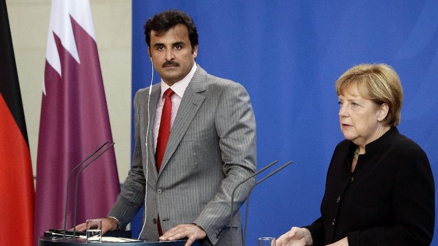 German Chancellor Angela Merkel, right, and the Emir of Qatar, Sheikh Tamim bin Hamad bin Khalifa al Thani, left, address the media during a joint press conference as part of a meeting at the chancellery in Berlin, Germany, Wednesday, Sept. 17, 2014. (AP Photo/Michael Sohn)