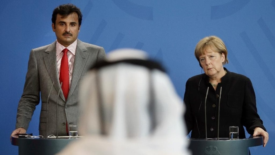 A journalist asks a question during a joint press conference of German Chancellor Angela Merkel, right, and the Emir of Qatar, Sheikh Tamim bin Hamad bin Khalifa al Thani, left, as part of a meeting at the chancellery in Berlin, Germany, Wednesday, Sept. 17, 2014. (AP Photo/Michael Sohn)