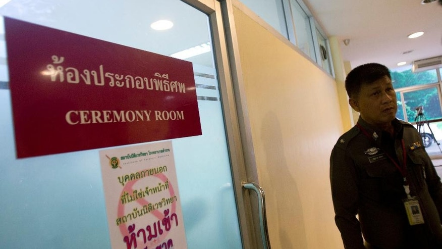 A Thai police officer stands outside a ceremony room as British Embassy officials are inside to examine the condition of the bodies of two murdered British tourists and to report it to their families at the Forensic Police Institute in Bangkok, Thailand, Wednesday, Sept. 17, 2014. Police on the scenic Thai resort island of Koh Tao in the Gulf of Thailand searched hotels and workers' residences Tuesday looking for clues into the slayings of two British tourists whose nearly naked, battered bodies were found on a beach a day earlier. (AP Photo/Sakchai Lalit)