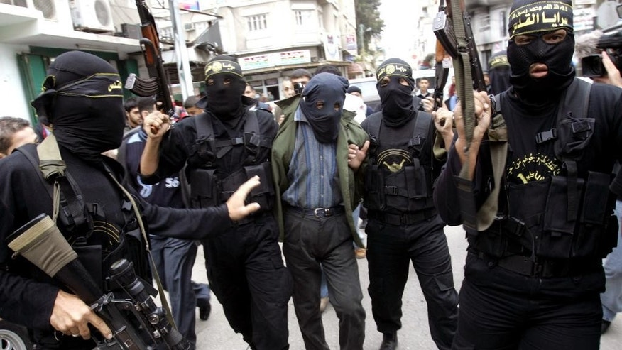 FILE - In this Sunday Nov. 5, 2006 file photo, Palestinian Islamic Jihad masked gunmen hold up their guns as they display one of two men whom they alleged were Palestinian collaborators for Israel in Gaza City. Hamas views collaborators in Gaza as a serious threat, holding them responsible for the assassination by Israel over the years of dozens of its top political leaders and military commanders. Israel, on the other hand, has historically relied on collaborators in its war against Palestinian militants and Palestinian activism in general, using methods that vary from entrapment and blackmail to cash and perks. (AP Photo/Khalil Hamra, File)