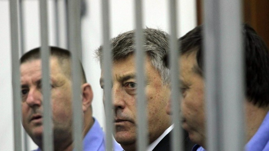 Central Bank of Albania governor Ardian Fullani, center, sits behind bars in a court room in Tirana Thursday Sept. 18, 2014.  The Albanian  Parliament has discharged central Bank of Albania governor Ardian Fullani, who is charged with abuse of office, for alleged mismanagement in connection with a multi-million dollar theft from the bank's reserves.  (AP Photo/Hektor Pustina)