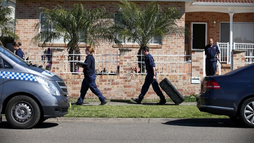 Police investigators work at a home at Guildford in suburban Sydney, Australia after about 800 federal and state police officers raided more than two dozen properties as part of the operation Thursday, Sept. 18, 2014. Australian police detained 15 people earlier on Thursday in a major counterterrorism operation, saying intelligence indicated a random, violent attack was being planned on Australian soil. (AP Photo/Rick Rycroft)