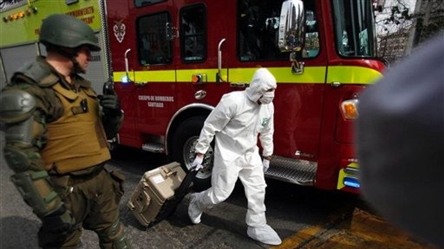 A police forensic expert arrives to the blast site at a subway station in Santiago, Chile, Monday, Sept. 8, 2014.