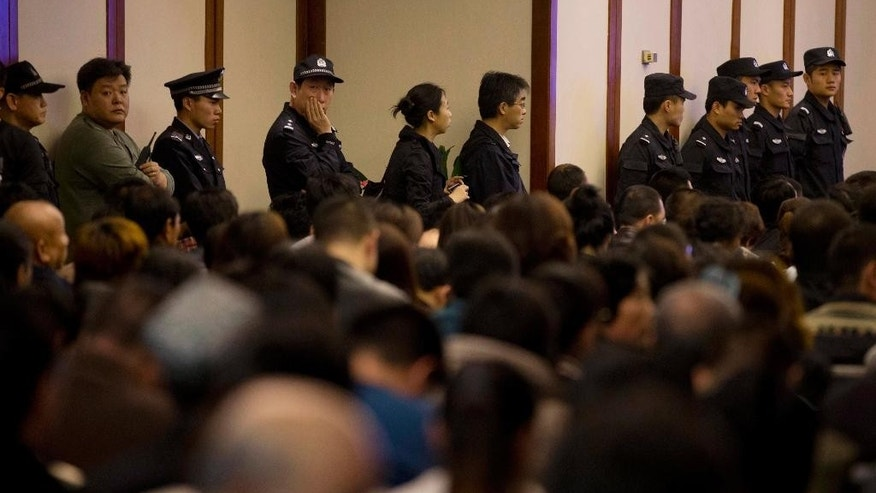 FILE - In this March 27, 2014 file photo, Chinese policemen stand watching the relatives of Chinese passengers on board Malaysia Airlines Flight 370 as they attend a briefing by Malaysian officials at a hotel in Beijing, China. China's leadership has long been wary of anyone capable of amassing a social following, especially after thousands of pro-democracy protesters in Tiananmen Square boldly challenged one-party rule in 1989. With social media now able to rapidly spread information, religious and human rights groups say Chinese leaders are further tightening controls by targeting people who show just the potential of emerging as social actors. (AP Photo/Andy Wong, File)
