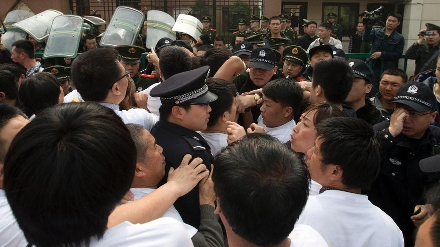FILE - In this March 25, 2014 file photo, relatives of Chinese passengers on board the Malaysia Airlines plane MH370 scuffle with Chinese police officers outside the Malaysian embassy in Beijing, China. China's leadership has long been wary of anyone capable of amassing a social following, especially after thousands of pro-democracy protesters in Tiananmen Square boldly challenged one-party rule in 1989. With social media now able to rapidly spread information, religious and human rights groups say Chinese leaders are further tightening controls by targeting people who show just the potential of emerging as social actors. (AP Photo/Ng Han Guan, File)