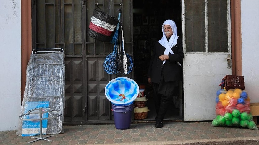 In this photo taken on Tuesday, Sept. 16, 2014,  Tayes , 86, a Druze shop owner stand in the entrance to his shop in Majdal Shams in Israeli-controlled Golan Heights near the border with Syria. For four decades, a multinational United Nations mission has quietly monitored the sleepy Golan Heights — providing a symbol of stability between bitter enemies as it enforced a truce between Israel and Syria. But as Syria has plunged into civil war and the peacekeepers themselves have become targets of al-Qaida-linked rebels, the U.N. observer force has begun to fall apart, leaving its future — and the prospects for ever establishing peace in this rugged area of the Middle East — in doubt.(AP Photo/Tsafrir Abayov)