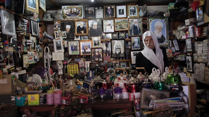 In this photo taken on Tuesday, Sept. 16, 2014,  Tayes , 86, a Druze shop owner, stands in  his shop in Majdal Shams in Israeli-controlled Golan Heights near the border with Syria. For four decades, a multinational United Nations mission has quietly monitored the sleepy Golan Heights — providing a symbol of stability between bitter enemies as it enforced a truce between Israel and Syria. But as Syria has plunged into civil war and the peacekeepers themselves have become targets of al-Qaida-linked rebels, the U.N. observer force has begun to fall apart, leaving its future — and the prospects for ever establishing peace in this rugged area of the Middle East — in doubt. (AP Photo/Tsafrir Abayov)