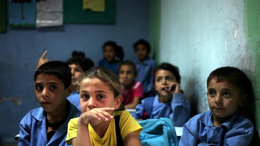 In this picture taken on Thursday, May 29, 2014, Syrian refugee students sit in their classroom at a Lebanese public school where only Syrian students attend classes in the afternoon, in Kaitaa village in north Lebanon. A report by the Britain-based Save the Children released Thursday, Sept. 18, 2014 says that nearly three million Syrian children are not attending school due to the war raging in their country. (AP Photo/Hussein Malla)