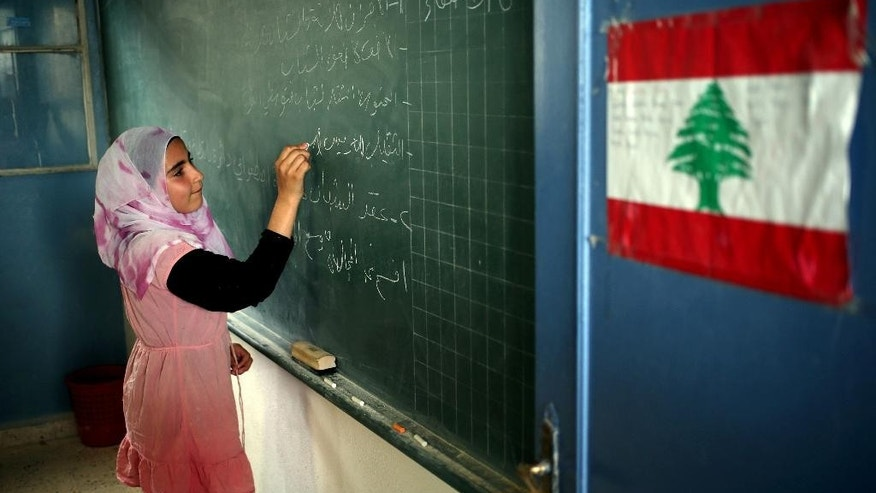 In this picture taken on Thursday, May 29, 2014, a Syrian refugee student writes on the board in her classroom, at a Lebanese public school where only Syrian students attend classes in the afternoon, in Kaitaa village in north Lebanon. A report by the Britain-based Save the Children released Thursday, Sept. 18, 2014 says that nearly three million Syrian children are not attending school due to the war raging in their country.(AP Photo/Hussein Malla)