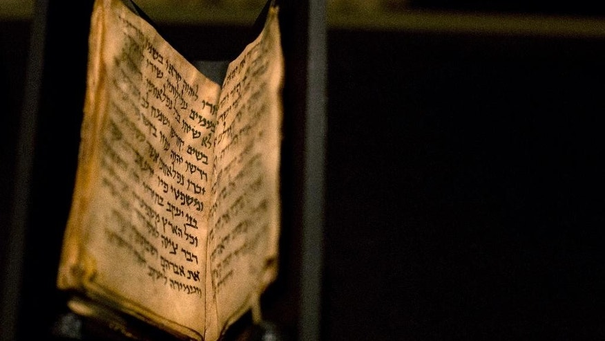 An ancient prayer book is seen on display at the Bible Lands museum in Jerusalem, Thursday, Sept. 18, 2014. An Israeli museum Thursday unveiled what it says in the oldest known Jewish prayer book in the world, dating back to the 9th century A.D. (AP Photo/Sebastian Scheiner)