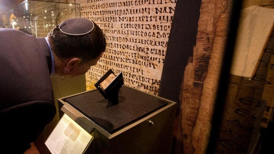 Israeli Parliament Speaker Yuli Edelstein looks at an ancient prayer book on display at the Bible Lands museum in Jerusalem, Thursday, Sept. 18, 2014. An Israeli museum Thursday unveiled what it says in the oldest known Jewish prayer book in the world, dating back to the 9th century A.D. (AP Photo/Sebastian Scheiner)