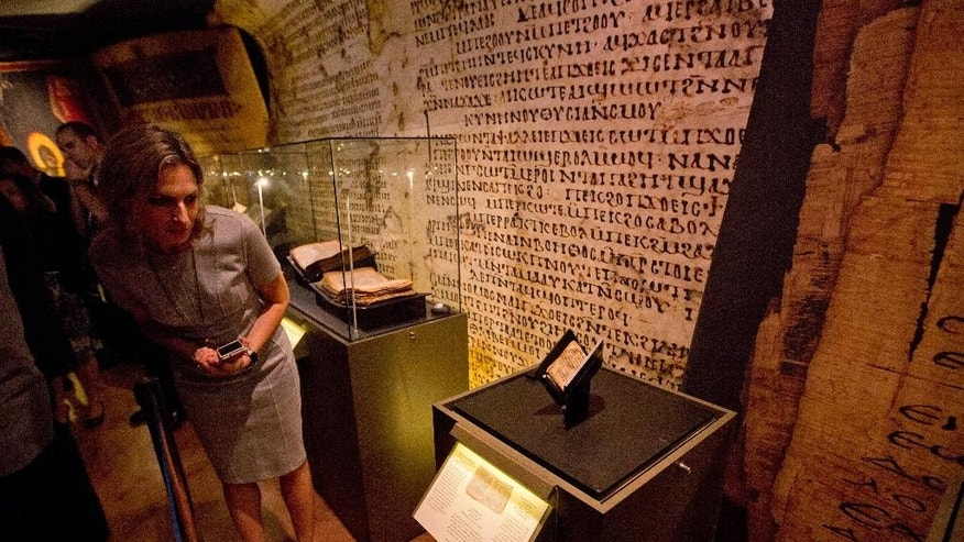 A museum worker looks at an ancient prayer book on display at the Bible Lands museum in Jerusalem, Thursday, Sept. 18, 2014. An Israeli museum Thursday unveiled what it says in the oldest known Jewish prayer book in the world, dating back to the 9th century A.D.  (AP Photo/Sebastian Scheiner)