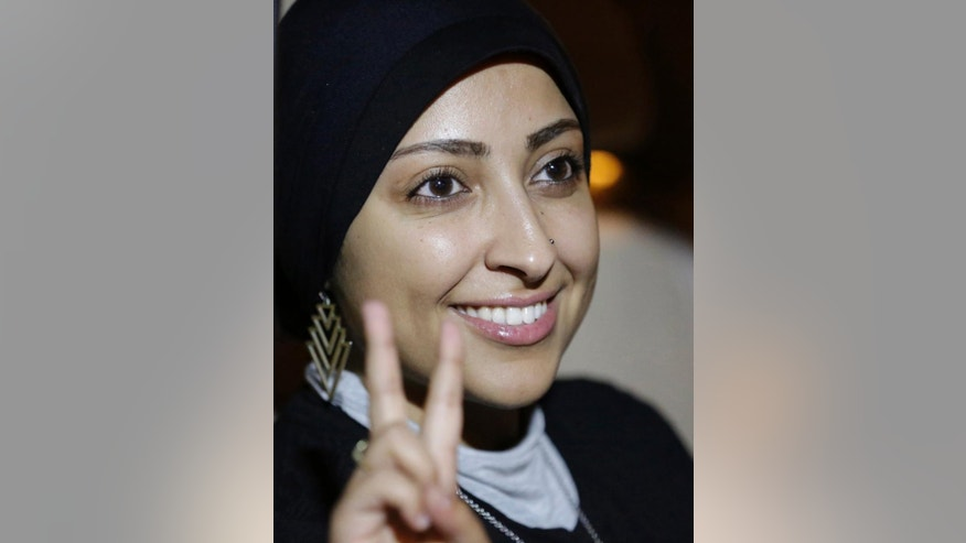 Human rights activist Maryam al-Khawaja flashes the victory sign outside a police station in Muharraq, Bahrain, Thursday, Sept. 18, 2014. Bahrain's Interior Ministry said Thursday that police have released human rights activist Maryam al-Khawaja, who was being held for questioning after her arrest on arrival in the Gulf Arab country last month. (AP Photo/Hasan Jamali)