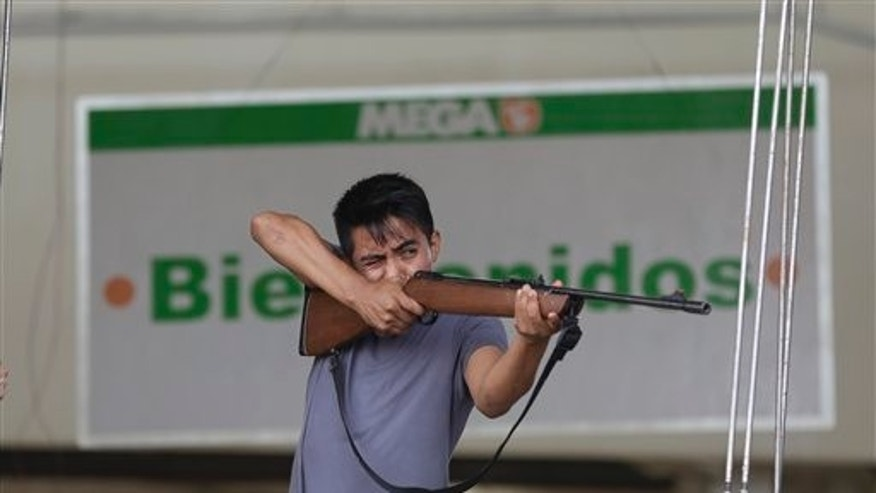 "An employee from Mega Supermarket fires an air rifle at people trying to loot the store in Los Cabos, Mexico, Tuesday, Sept. 16, 2014. The sign in the background reads in Spanish ""Welcome.""  According to employees the supermarket donated all the food in the store and established a system by which every person had 5 minutes to get whatever they could for free. Fights broke as other people inciting the crowd to loot. Desperate locals and tourists were in survival mode in the resort area of Los Cabos also on Wednesday, with electrical and water service still out three days after Hurricane Odile made landfall as a monster Category 3 storm. (AP Photo/Victor R. Caivano)"
