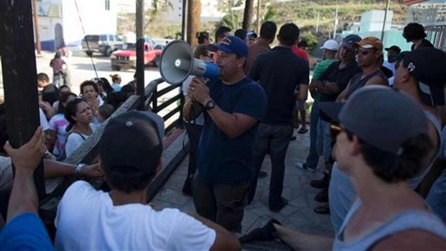 A man uses a bull horn to call on residents of a neighborhood to prepare themselves against looters and criminal gangs after the passing of hurricane Odile in San Jose de los Cabos, Mexico, Wednesday, Sept. 17, 2014. After Odile roared past, residents of the resort state of Baja California Sur struggled with a lack of power and running water and formed long lines for emergency supplies. There were scattered reports of looting.  (AP Photo/Dario Lopez-Mills)