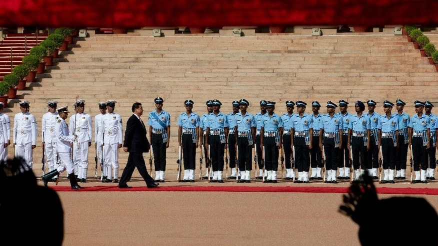 Chinese President Xi Jinping inspects a guard of honor during a ceremonial reception in New Delhi, India, Thursday, Sept. 18, 2014. Xi and Indian Prime Minister Narendra Modi will hold talks aimed at boosting trade and Chinese investment even as their troops face-off along their disputed border in the Himalayas.  (AP Photo/Manish Swarup)