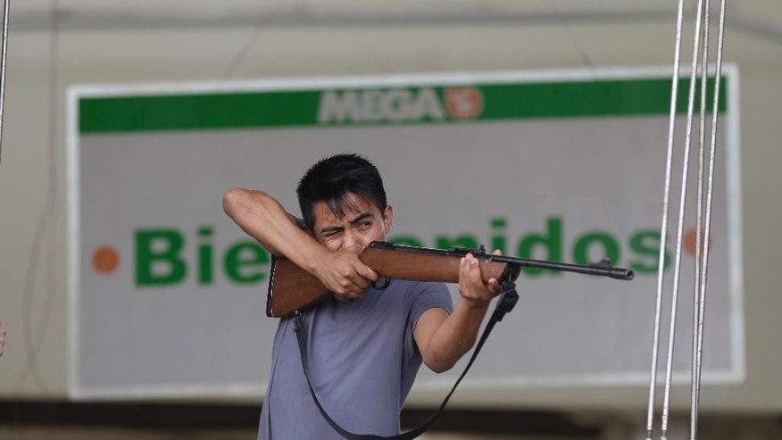 Sept. 16, 2014: An employee from Mega Supermarket fires an air rifle at people trying to loot the store in Los Cabos, Mexico.