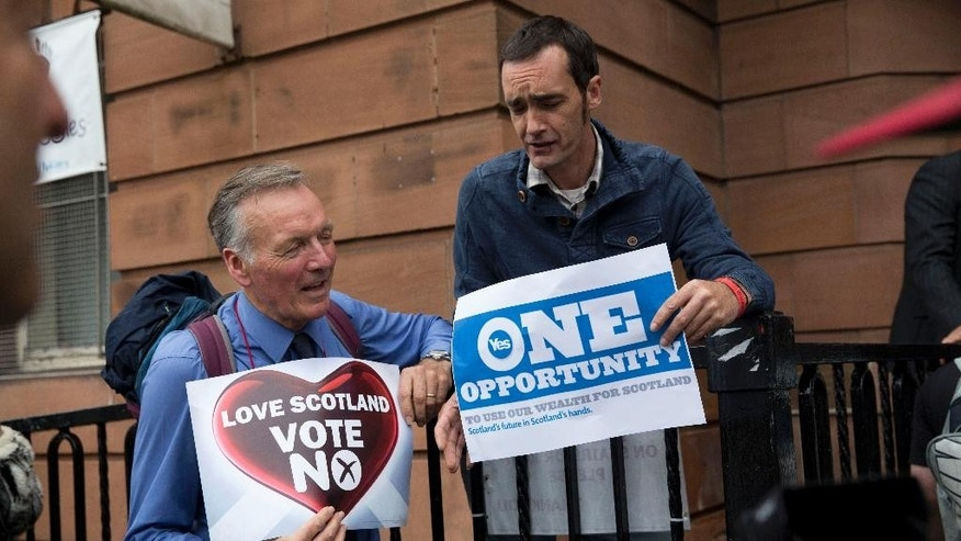 "FILE - In this Wednesday, Sept. 17, 2014, file photo, a ""No"" campaign supporter and a ""Yes"" campaign supporter chat holding posters after a No campaign event where a number of speeches were made by different people and politicians in Glasgow, Scotland. Breaking up is hard to do, especially after 300 years. The people of the United Kingdom will find out just how hard if Scotland votes for independence on Thursday. (AP Photo/Matt Dunham, File)"