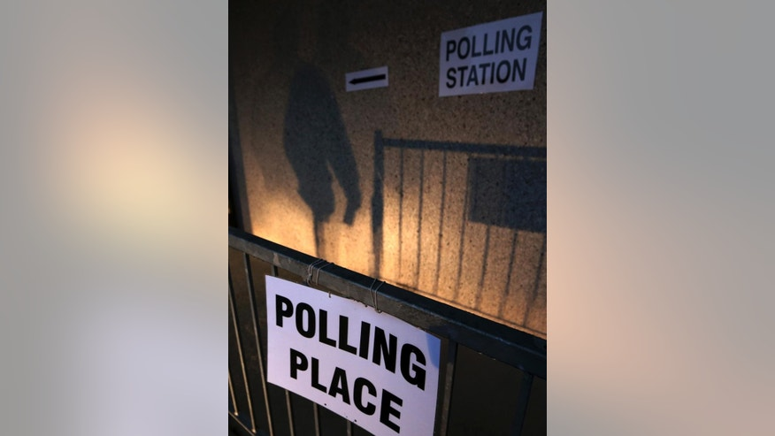 The shadow of a voter is cast after as he leaves after voting at Ritchie Hall in Strichen, Scotland, Thursday, Sept. 18, 2014. Polls opened across Scotland in a referendum that will decide whether the country leaves its 307-year-old union with England and becomes an independent state. (AP Photo/Scott Heppell)