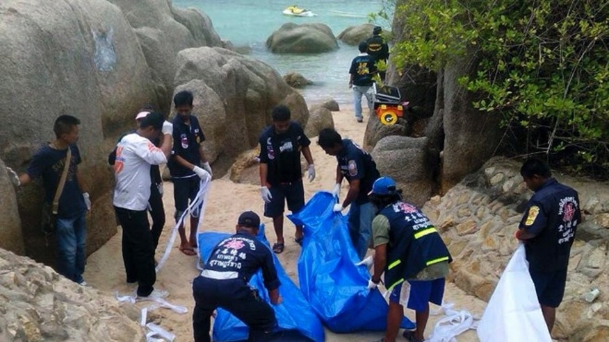 Sept. 15, 2014: Thai officers work near the bodies of two British tourists on a beach in Surat Thani  province, southern Thailand. Their bodies were discovered early Monday on a beach on Koh Tao, a small island known for its diving sites and serene beaches, police said.