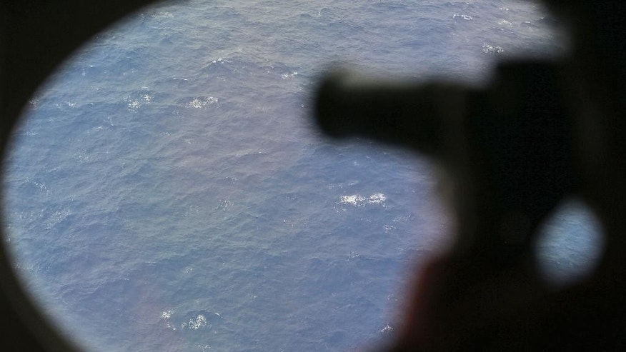 FILE - In this April 1, 2014 file photo, an observer on a Japan Coast Guard Gulfstream aircraft takes photos out of a window while searching for the missing Malaysia Airlines Flight 370 in Southern Indian Ocean. Crews will resume the hunt for missing Malaysia Airlines Flight 370 at the end of the month, and will begin the search in an area farther south than initially planned. Australian Transport Safety Bureau Chief Commissioner Martin Dolan said on Friday, Sept. 19, 2014 that the first of three ships planning to scour the Indian Ocean for the plane should begin searching Sept. 30. (AP Photo/Rob Griffith, Pool, File)