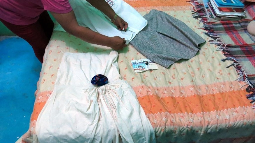 In this Sept. 15, 2014 photo, a woman who did not want to give her name for fear of reprisals, lays out the clothes of her late 15-year-old daughter Erika Gomez Gonzalez, on a bed at her home in Arcelia, Mexico. The woman says she witnessed her child's death when army soldiers fired first at an armed group at a grain warehouse on June 30 in the town of San Pedro Limon, Mexico. She said one man died in the initial shootout, when the rest of the gunmen surrendered on the promise they would not be hurt. She recalls that her daughter, who was face down in the ground with a bullet in her leg, was rolled over while she was still alive and shot more than half a dozen times in the chest. The mother said she arrived to the warehouse the day before the shooting, in an attempt to take her daughter home, but gang members wouldn't let her. (AP Photo/Eduardo Castillo)