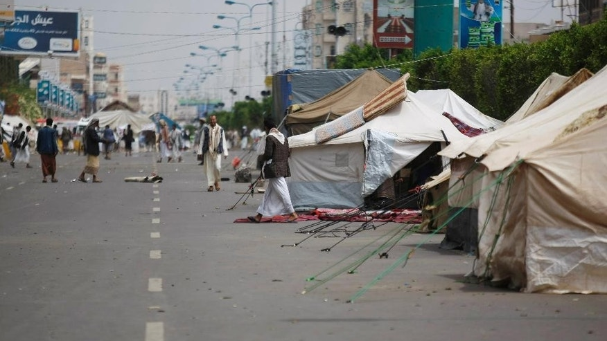 In this photo taken on Wednesday, Sept. 17, 2014, Hawthi Shiite protesters walk near tents at a sit-in in a main road leading to the airport in Sanaa, Yemen. Security officials say Shiite rebels have reached a suburb of Yemen's capital where they are fighting Sunni militias and besieging a university run by one of the nation's best known Sunni radicals. The officials say Thursday's fighting on Sept. 18, 2014 in Shamlan has forced thousands to flee their homes, but they have no word on casualties. They say the rebels, known as Hawthis, are surrounding the Iman University, an institution long viewed as a primary breeding ground for militants. (AP Photo/Hani Mohammed)