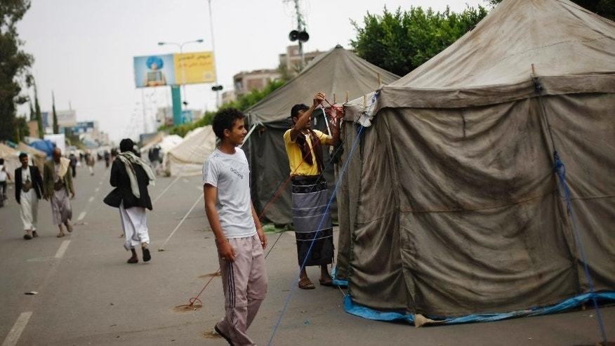 In this photo taken on Wednesday, Sept. 17, 2014, Hawthi Shiite protesters set up a tent at a sit-in in a main road leading to the airport in Sanaa, Yemen. Security officials say Shiite rebels have reached a suburb of Yemen's capital where they are fighting Sunni militias and besieging a university run by one of the nation's best known Sunni radicals. The officials say Thursday's fighting on Sept. 18, 2014 in Shamlan has forced thousands to flee their homes, but they have no word on casualties. They say the rebels, known as Hawthis, are surrounding the Iman University, an institution long viewed as a primary breeding ground for militants. (AP Photo/Hani Mohammed)