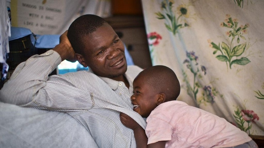 In this photo taken Wednesday, Aug. 27, 2014, former Westgate Mall security guard David Odhiambo, 36, recounts his experience as his daughter Benta, 4, plays with him in his tiny, one-room house where he lives with his wife and five children in the Kawangware slum of Nairobi, Kenya. Odhiambo was one of the blue-uniformed security guards tasked with protecting Nairobi's Westgate Mall one year ago when four heavily armed terrorists attacked, earning him two bullets in the head. (AP Photo/Ben Curtis)