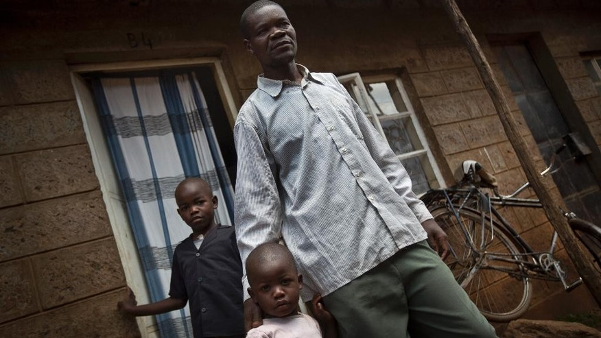 In this photo taken Wednesday, Aug. 27, 2014, former Westgate Mall security guard David Odhiambo, 36, stands with his daughter Benta, 4, center, and son Isaac, 7, left, outside his tiny, one-room house where he lives with his wife and five children in the Kawangware slum of Nairobi, Kenya. Odhiambo was one of the blue-uniformed security guards tasked with protecting Nairobi's Westgate Mall one year ago when four heavily armed terrorists attacked, earning him two bullets in the head. (AP Photo/Ben Curtis)