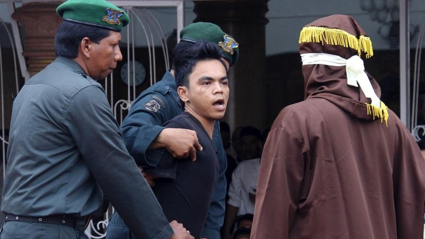 A man convicted of gambling watches an Islamic Shariah law official, right, after being whipped with a rattan cane by him in Banda Aceh, Aceh Province, Indonesia, Friday, Sept. 19, 2014. Indonesian authorities publicly caned eight men who were convicted of gambling in conservative Aceh province. A state prosecutor read out their punishment, and a masked man wearing robes used a thin rattan cane to whip their backs five times each. (AP Photo/Heri Juanda)