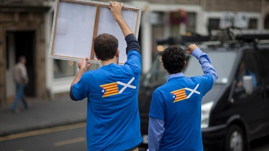 "David Aguilar, left, and Aleix Sarri from Catalonia, who are visiting Scotland to support the Scottish independence referendum, gesture and hold up a placard supporting a Yes vote at passing motorists in Edinburgh, Scotland, Thursday, Sept. 18, 2014.  Their t-shirts are printed with a design showing an ""estelada"" Catalan pro-independence flag, left, next to a Scottish Saltire flag. Polls have opened across Scotland in a referendum that will decide whether the country leaves its 307-year-old union with England and becomes an independent state. (AP Photo/Matt Dunham)"
