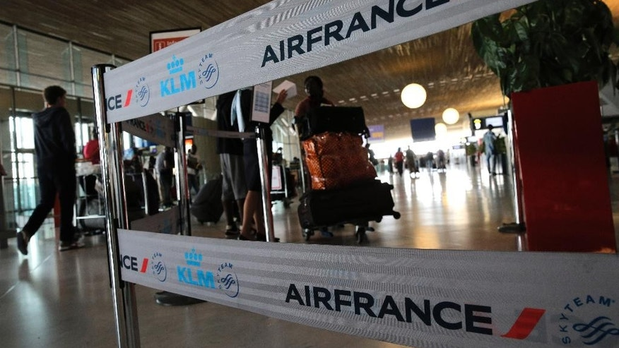 Travellers walk past an Air France desk at Paris Charles de Gaulle airport, in Roissy, near Paris, Wednesday, Sept. 17, 2014. Air France canceled at least half its flights around the world on Monday as pilots began a weeklong strike, highlighting the trouble Europe's flagship airlines face in keeping up with low-cost competitors. (AP Photo/Christophe Ena)