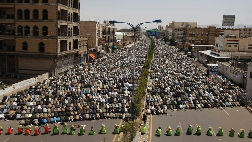 Hawthi Shiite rebels hold Friday prayers during a demonstration demanding the government to step down in Sanaa, Yemen, Friday, Sept. 19, 2014. Shiite rebels and Sunni militiamen battled in the streets of the Yemeni capital for a second day Friday in fighting that has killed at least 120 people, driven thousands from their homes and virtually shut down the country's main airport. The battles are raising fears of greater sectarian conflict, unseen for decades in Yemen. (AP Photo/Hani Mohammed)