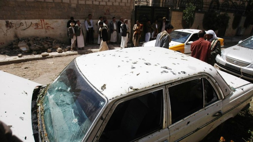 People gather near a car damaged by a mortar shell during fighting between government forces and Hawthi Shiite rebels in Sanaa, Yemen, Friday, Sept. 19, 2014. Shiite rebels and Sunni militiamen battled in the streets of the Yemeni capital for a second day Friday in fighting that has killed at least 120 people, driven thousands from their homes and virtually shut down the country's main airport. The battles are raising fears of greater sectarian conflict, unseen for decades in Yemen. (AP Photo/Hani Mohammed)