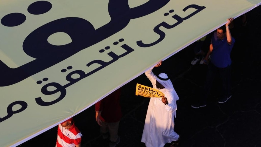 "Pro-democracy protesters hold up a huge banner and carry signs during a march in Budaiya, Bahrain, just outside the capital of Manama, Friday, Sept. 19, 2014. Thousands of opposition supporters have rallied in the tiny island nation of Bahrain to protest a proposal outlined by the country's leadership related to legislative, security and judicial reforms. The banner and the yellow sign refer to upcoming parliamentary elections and both read, in English and Arabic: ""Boycott until democratic demands are fulfilled."" (AP Photo/Hasan Jamali)"