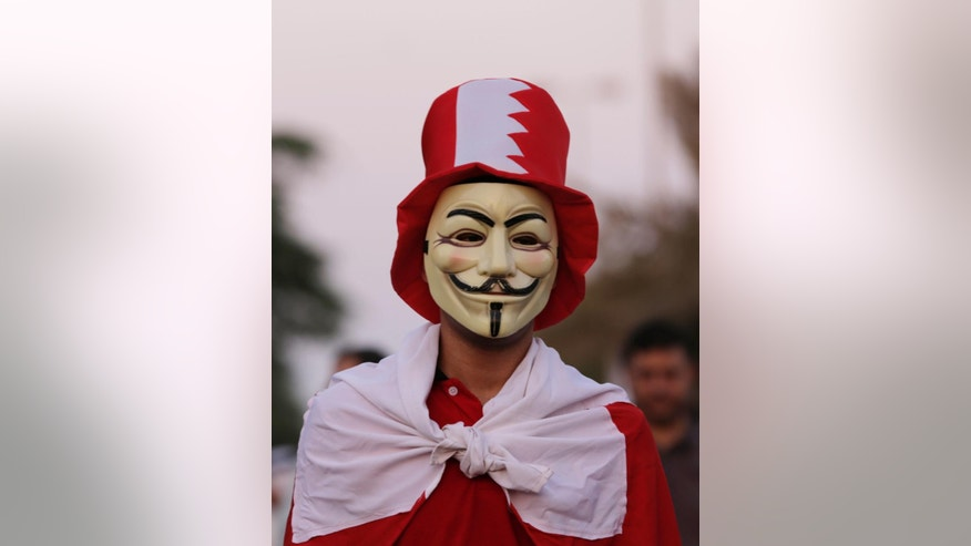 A Bahraini pro-democracy protester wears national flags and colors and a Guy Fawkes mask during a march in Budaiya, Bahrain, just outside the capital of Manama, Friday, Sept. 19, 2014. Thousands of opposition supporters have rallied in the tiny island nation of Bahrain to protest a proposal outlined by the country's leadership related to legislative, security and judicial reforms. (AP Photo/Hasan Jamali)
